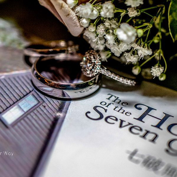 Wedding ring resting on a House of the Seven Gables pamphlet with Flowers resting gently above it.