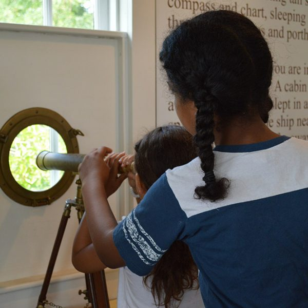 A toddler and young girl are inside a building looking through a telescope that looks outside.