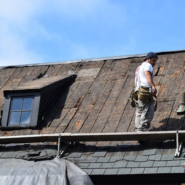 Two men with hats replacing and fixing the roof on the Beckett House.