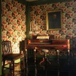 A parlor in the House of the Seven Gables with flower wallpaper, piano, portrait, and chair.