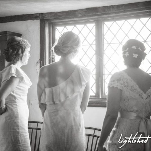 A bride and two bridesmaids staring out of the diamond pane windows in the Hooper-Hathway House