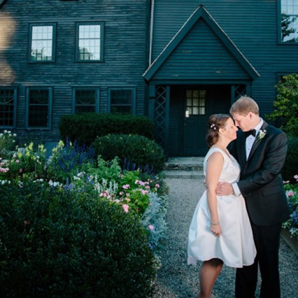 A man and a woman looking into each others eyes on their wedding day standing in front of the House of the Seven Gables.