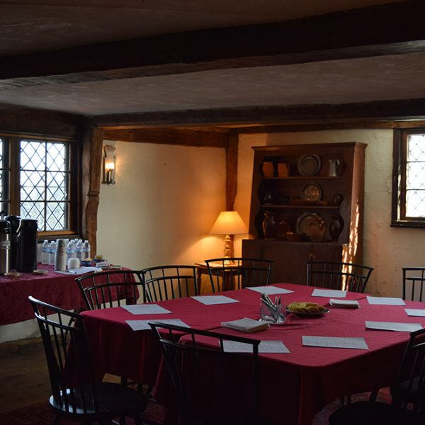 Meeting room at the House of the Seven Gables displaying a table with chairs and refreshments on another table.