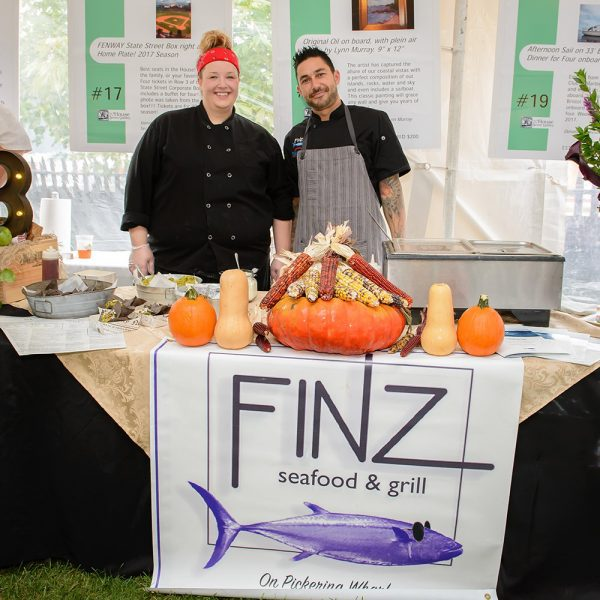 Two chefs from Finz Seafood and Grill Restaurant standing behind a display table with different vegetables on table.