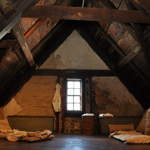 Interior view of the House of the Seven Gables attic with blankets, pillow, and one window.