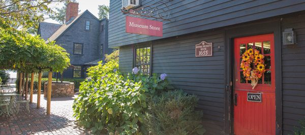 Exterior view of the House of the Seven Gables Museum store with bushes and red door on a sunny day. This is a great, local shop for gifts.