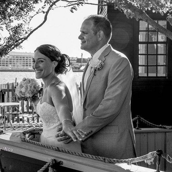 A husband and bride standing outside on the deck beside the ocean smiling.