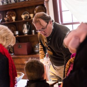 Man talking with family at the Living History lab at the House of the Seven Gables.
