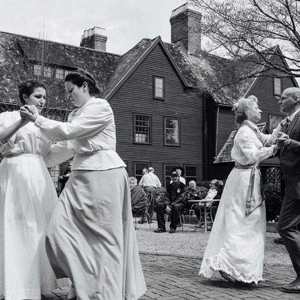 Historic black and white picture of four people dancing outside of the House of the Seven Gables.