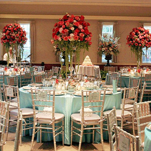 A wedding reception room with light blue tablecloth and big vase in the center with more than a dozen red and pink flowers.