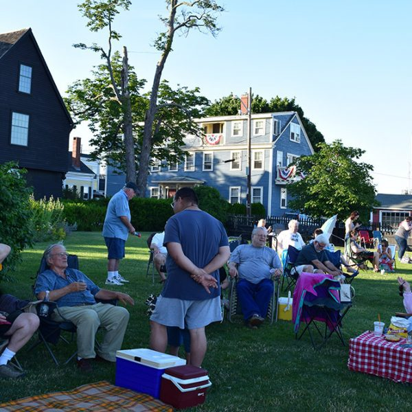 Many people having picnics on the grass outside of the Seven Gables.