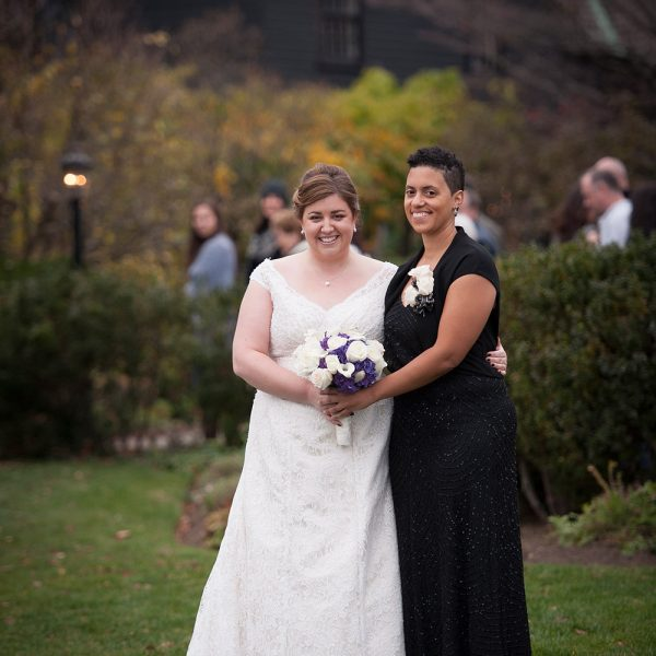 Two women posing for their wedding photos outside on a field. One woman is wearing a white long dress and the other is wearing a long black dress.