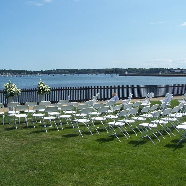 Rows of white chairs prepared for a wedding.