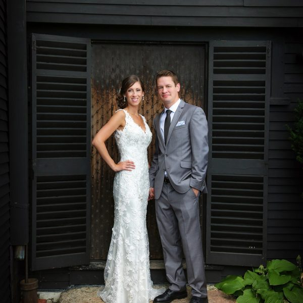 A bride and groom standing and posing for a picture in front of black wooden house.