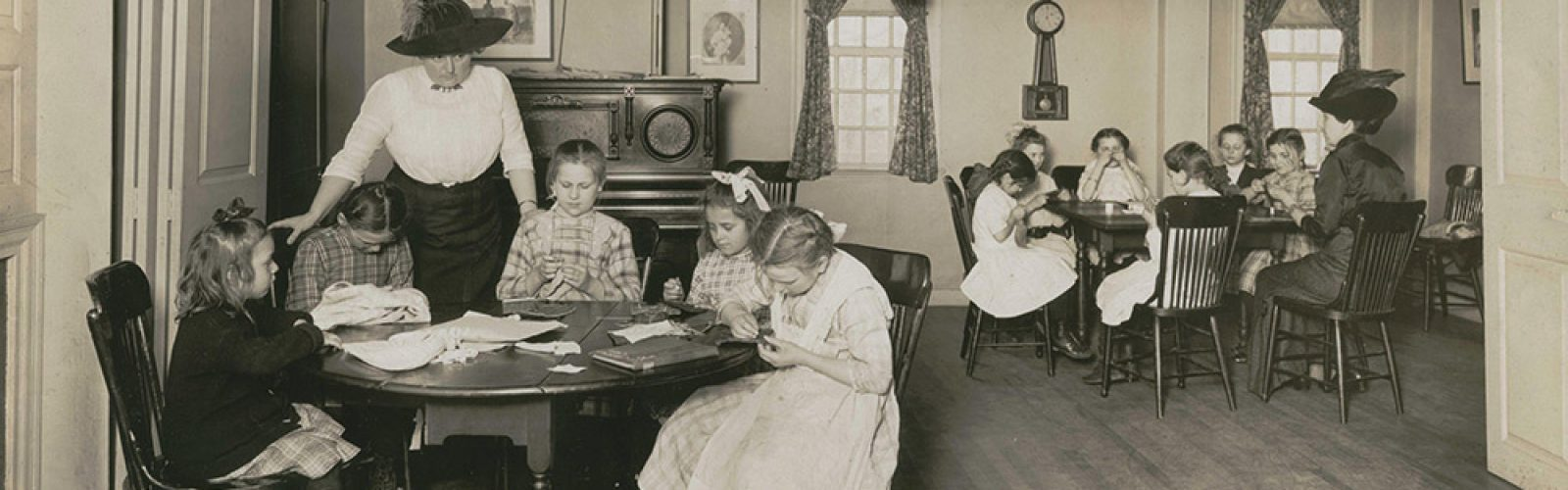 Caroline Emmerton is standing talking to children as they write around a table in the House of the Seven Gables.