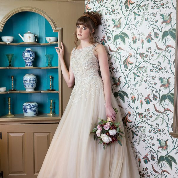 Beautiful bride stands as she poses in a room at the House of the Seven Gables. She stands next to traditional wallpaper and blue wooden cabinet.