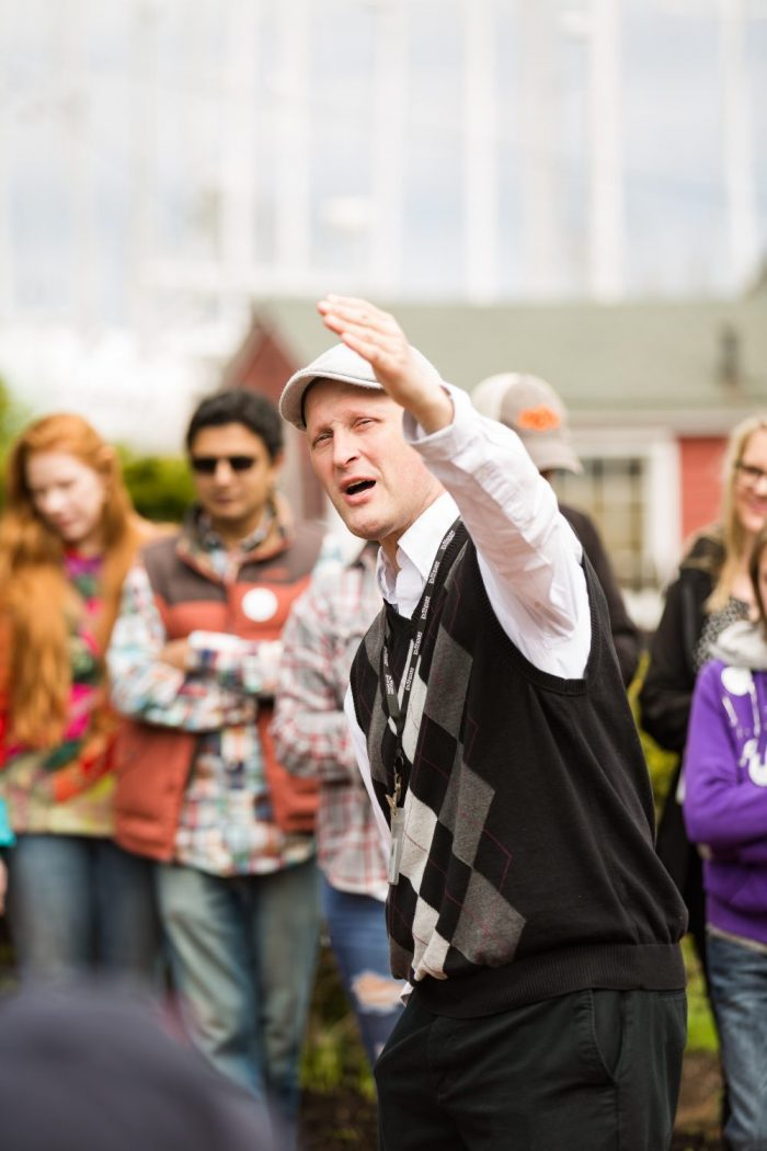Tour Guide pointing hand upwards while address tour group | Group Tours
