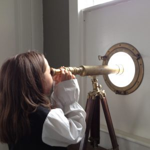 Child peeking through old telescope | Kids' Cove at the Counting House