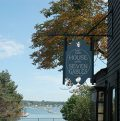The house of Seven Gables sign with a view of the ocean on a sunny day.