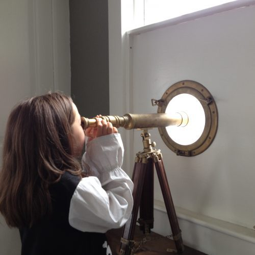 Young person looking through a telescope at The Gables