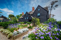 Exterior image of The House of the Seven Gables with the garden in full bloom