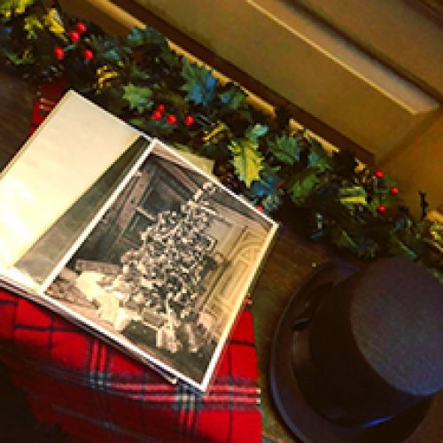 An antique photograph of a Christmas tree along with a top hat and scarf