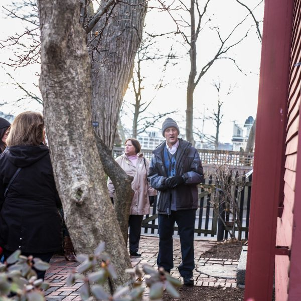 A guide sharing information with visitors outside of the Nathaniel Hawthorne Birthplace