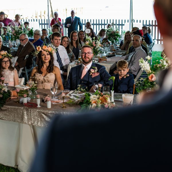 A wedding party listening to a toast