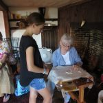 A young visitor to The House of the Seven Gables observes rug hooking in action