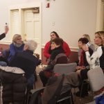 A group of people have a conversation at The House of the Seven Gables