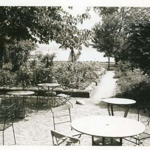Black and white photograph of gardens featuring raised beds and lawn furniture.