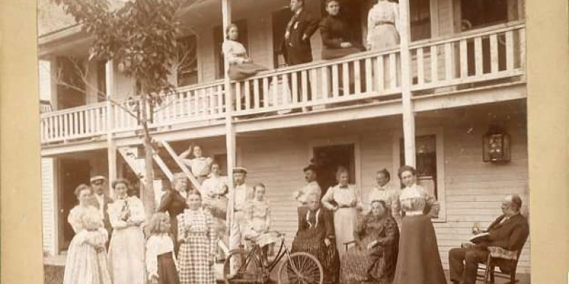 Photograph of adults and children arranged on the front porch, stairs, and balcony of a building