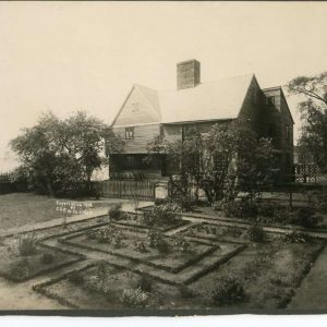 A black and white photograph of a house with peaked roof and a knot-patterned garden.