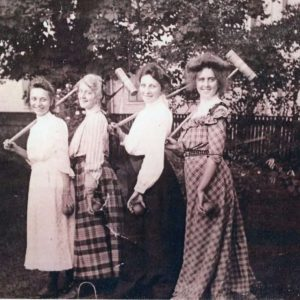 A black and white photograph of four women posing with croquet mallets.