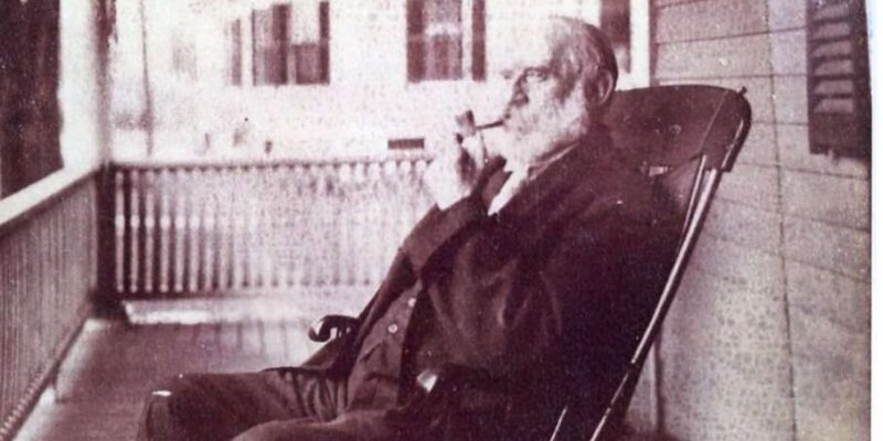 A black and white photograph of a man in a chair smoking a pipe.
