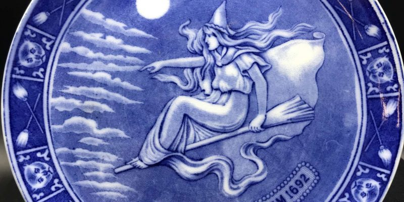 plate with a blue and white image of a witch flying on a broom