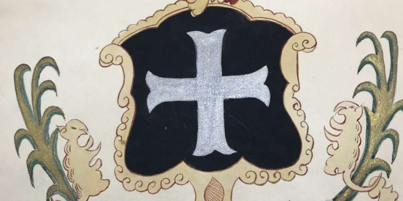 Colorful family crest including a silver cross in a black background, a helmet, a crown, and a small horse