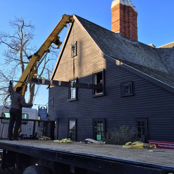 photograph of the new beam being hoisted by a crane through a window at The House of the Seven Gables during the 2016 reconstruction project.