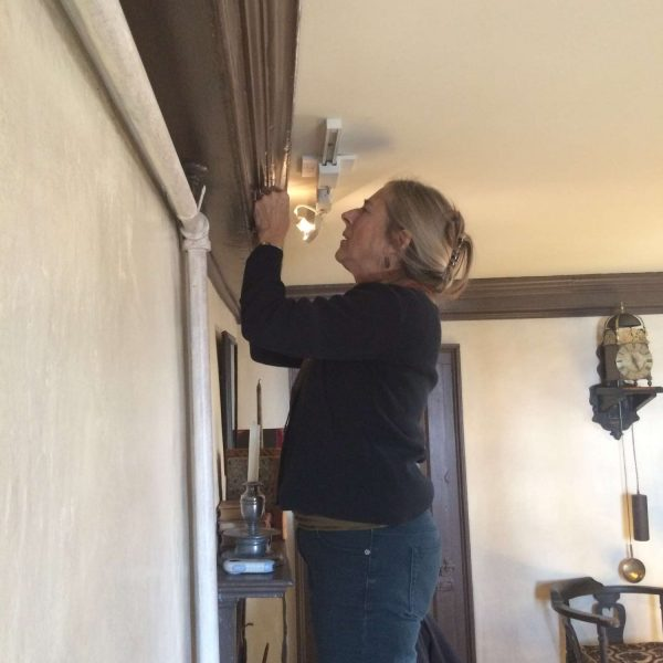 photograph of Christine Thomson taking paint samples in the accounting room at The House of the Seven Gables during the 2016 restoration project.