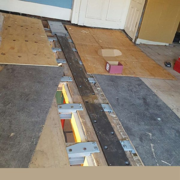photograph of the steel beam and floor joists supports in place during the 2016 restoration of the dining room chamber at The House of the Seven Gables.