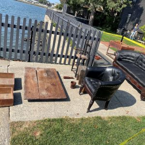Photo of collection objects from the Nathaniel Hawthorne Birthplace being treated for mold with UV rays on the walkway by the seaside lawn.